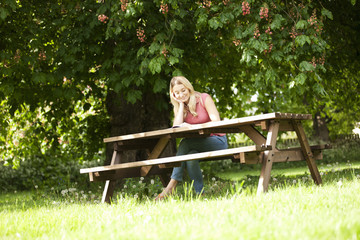 A young woman sitting on a garden bench reading a book, smiling