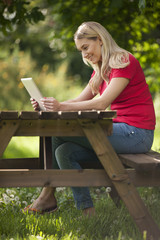 A young woman sitting at a bench using a digital tablet, smiling