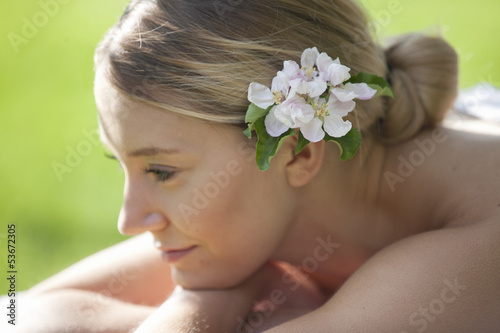 A young woman with blossom in her hair, thinking