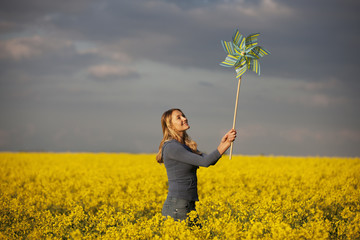 A young woman standing in a rape seed field holding a windmill