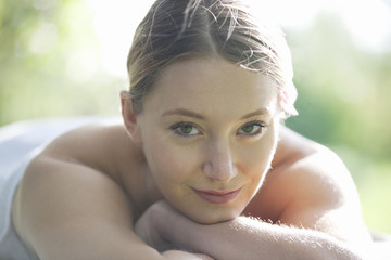 A young woman laying on a massage table, looking to camera
