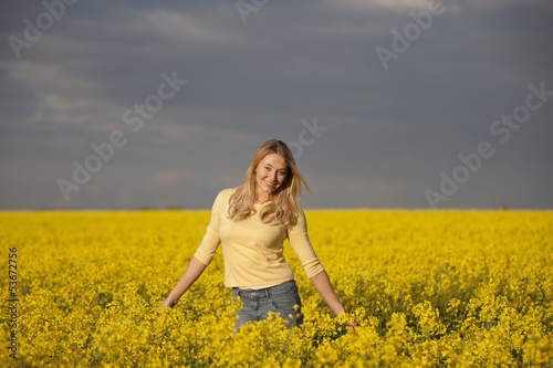 A young woman standing in a rape seed field