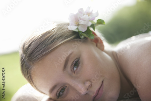 A young woman laying down with apple blossom in her hair