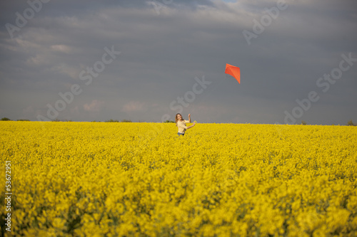 A young woman flying a kite in a rape seed field