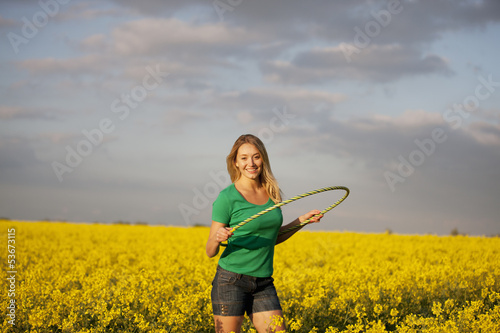 A young woman hula hopping in a rape seed field