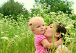 Beautiful woman with a baby in a field of flowers