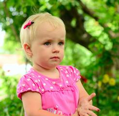 cute little girl sitting in the green grass