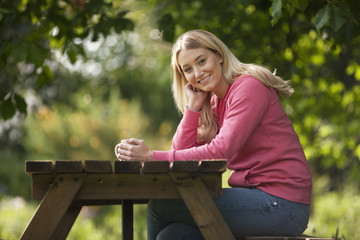A young woman sitting at a garden bench with a hot drink
