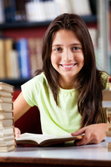 Happy Schoolgirl Sitting At Table In Library