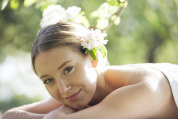 A young woman wearing blossom in her hair, looking to camera