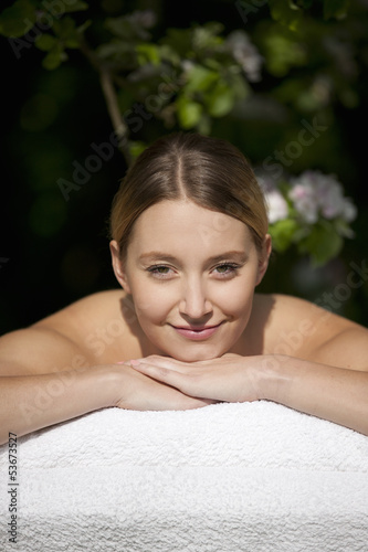 A young woman laying on a massage table, smiling