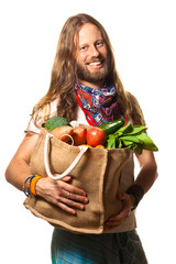 Smiling man holding a bag of organic fruit and vegetables.