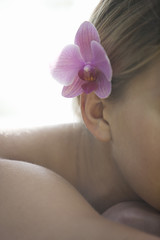 A young woman wearing a pink orchid in her hair