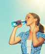 woman drinks water from a bottle in the summer outdoors on the s
