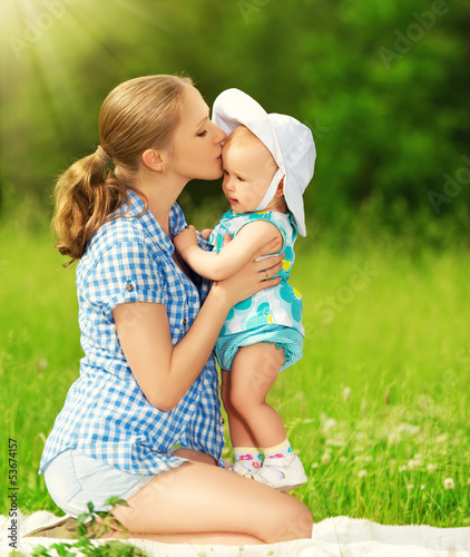 happy family on a walk. mother kissing baby