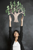 Asian woman reaching for chalk money tree drawn on blackboard.