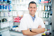 cheerful smiling pharmacist chemist man standing in pharmacy  - 53674786