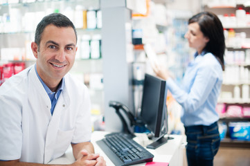 cheerful smiling pharmacist chemist man standing in pharmacy