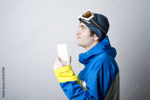 Young man holding blank lift admission ticket