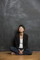 Happy Asian woman standing in front of a blank chalkboard.