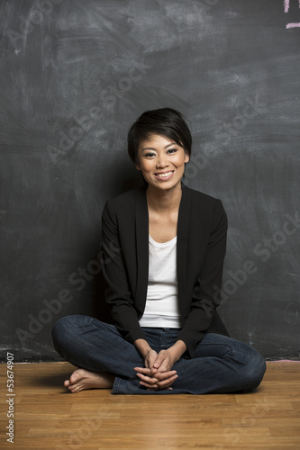 Happy Asian woman standing in front of a blank chalkboard.