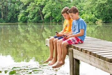 Zwei jugendliche Freunde mit Smartphone am idyllischen Teich
