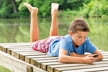 Jugendlicher / Kind mit Smartphone am idyllischen Teich