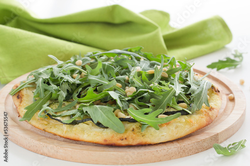 Pizza with mozzarella cheese, arugula and nuts.