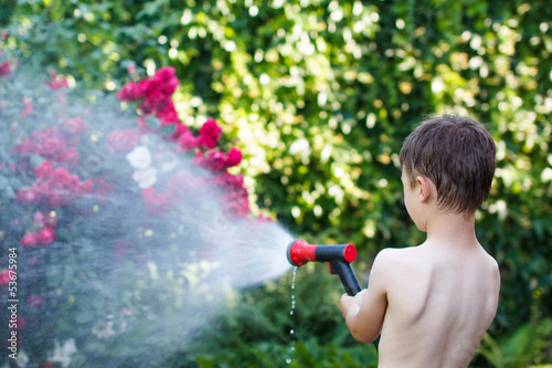 Little boy irrigate in garden