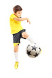 Full length portrait of a kid in sportswear shooting a ball