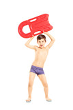 Full length portrait of a boy holding a swimming float
