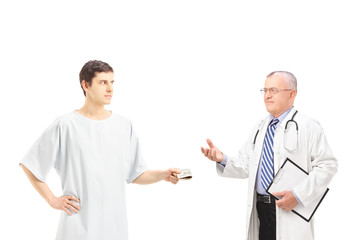 Male patient in hospital gown offering bribe to a medical doctor