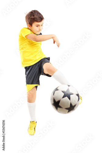 Full length portrait of a kid in sportswear shooting a ball