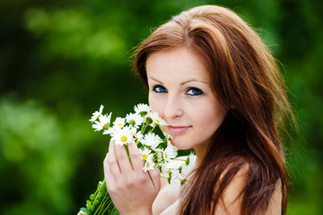 Beautiful Blue Eyed Woman Holding Flowers and smiling to camera
