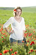 Young casual woman relaxing in poppy field