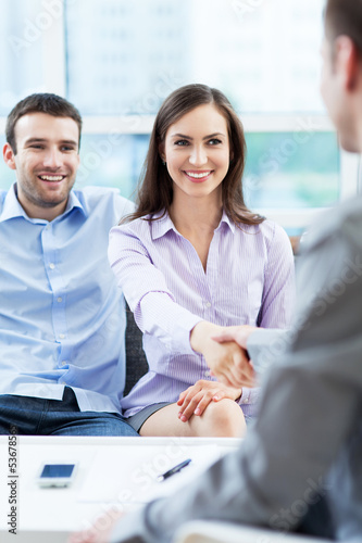 Couple shaking hands to real-estate agent at home