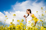 Beautiful Woman in white dress holding a rape flower. Rape Field