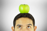 Young man looking up to apple on his head