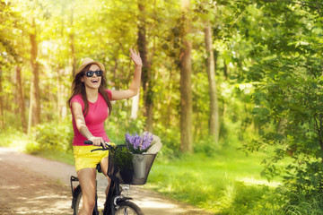 Beautiful woman waving to someone during cycling