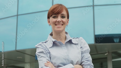 Portrait of happy businesswoman smiling near skyscraper