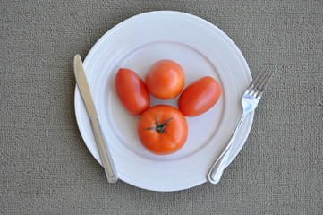 Tomatoes in plate with fork and knife