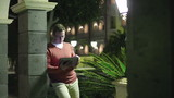 Young man in tourist resort working with tablet computer at nigh