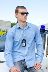 Young handsome male FBI agent near the car