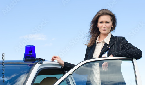 Young female FBI agent standing near car open door