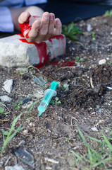 Bloody hand and syringe near it. Crime scene