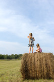 Two girls stand on haystack