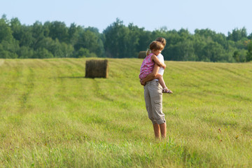 Mother and child in green field in the summer day