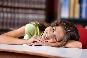 Thoughtful Schoolgirl Leaning On Table In Library