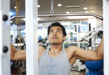 Asian man using lat pulldown machine