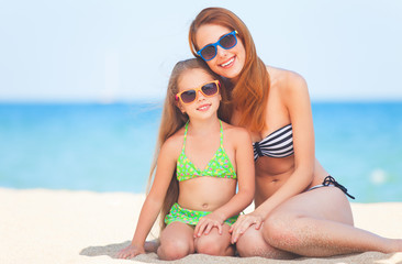 Beautiful mother and little daughter at tropical beach